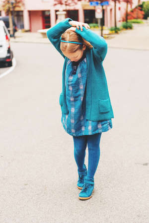 Outdoor fashion portrait of adorable little girl of 8-9 year old, wearing blue clothes and shoes Stock Photo