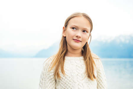 Cute little 8 year old girl playing by the lake on a very windy day, wearing warm white knitted pullover, high key image