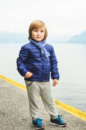 Outdoor portrait of adorable little blond 4-5 year old boy, wearing blue jacket and scarf, standing by the lake on a cloudy day, early spring Stock Photo