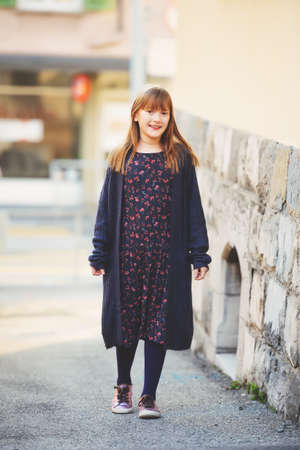 Street fashion portrait of young 8-9 year old girl wearing long dress, dark purple knitted cardigan, tights and modern sneakers shoes Stock Photo