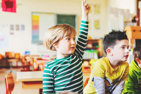 Two concentrated 4-5 year old boys in classroom, kid raising hand on lesson