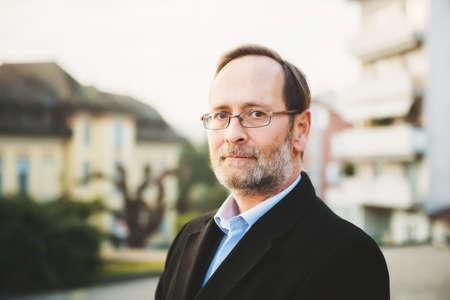 Buitenportret van 50 jarige man met zwarte jas en bril Stockfoto - 72944545