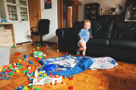 Adorable 1 year old baby boy with funny facial expression playing in a very messy living room Standard-Bild