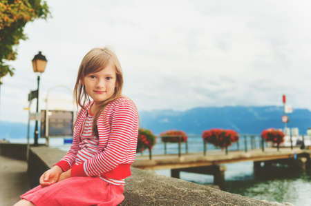 Cute 7 year old little girl resting by Lake Geneva