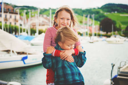 Two little kids playing together by lake Geneva on a very windy day, hugging each other