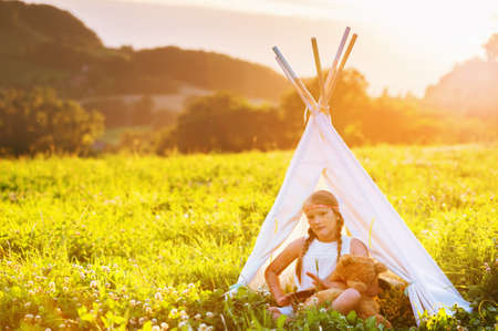 Happy kid girl sitting in a tent on a nice warm evening, playing drum music. Archivio Fotografico