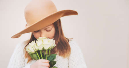 Pretty little girl wearing a hat, holding bouquet of white roses, standing against beige background