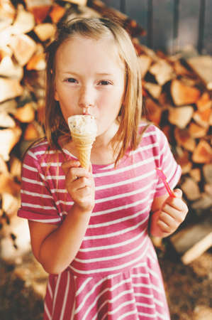 Cute little 6 year old girl eating ice cream outdoors, wearing pink stripe dress, summer pleasures for kids