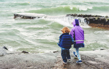 Group of two little kids playing by lake Geneva on a very windy day, Switzerland