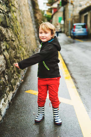 Little boy playing outdoors in early spring, walking next to road, wearing black waterproof jacket, red trousers and rain boots