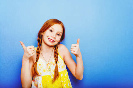 Studio shot of young preteen 9-10 year old redhead girl wearing yellow top, standing against blue purple background, big thumbs up Stock Photo