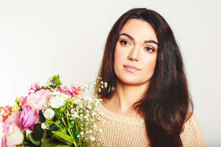Close up portrait of 35-40 year old woman with black hair, holding big bouquet of spring flowers, standing against white background Stock Photo