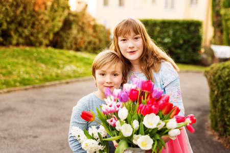 ittle: Ittle boy and his big sister holding big beautiful bouquet of colorful tulips