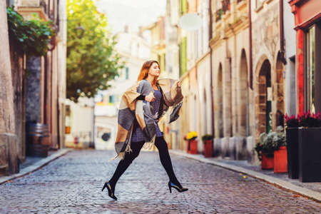 Young fashion 20 year old girl with red hair running down the street, wearing light dress, black tights, high heel shoes and warm plaid jacket Stock Photo
