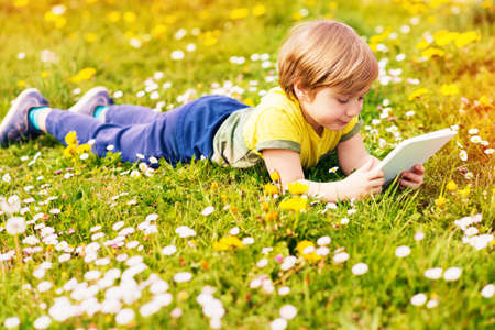 niños en recreo: Happy little kid boy playing tablet PC outdoors in the park on a very sunny day