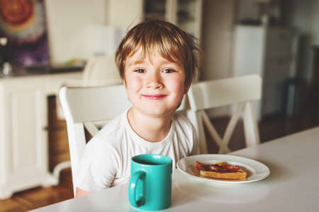 Cute little boy eating his toast with jam and hot chocolate for breakfast
