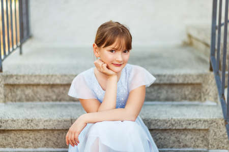 Sweet little preteen girl wearing party dress, sitting on stairs Stock Photo