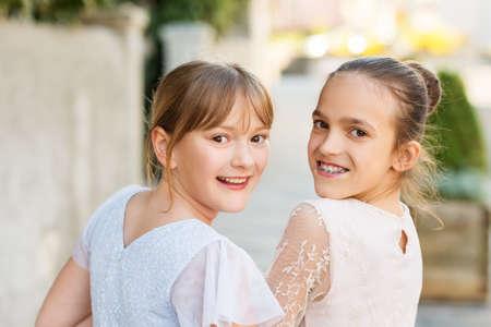 Retrato al aire libre de dos chicas dulces niño con vestidos de fiesta