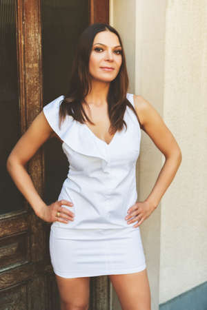 Beautiful slim woman posing outdoors, wearing white dress