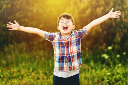 Happy kid boy of 6 year old having fun outdoors wearing blue plaid shirt, arms wide open