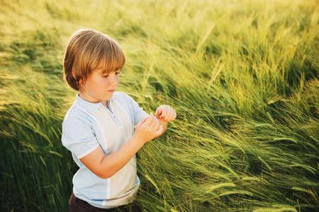 Dolce ragazzino che gioca nel campo di grano al tramonto in estate Archivio Fotografico - 80184602