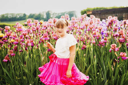 Cute little girl playing in Iris flower garden on a nice summer day, wearing white shirt and bright pink tutu skirt Stock Photo