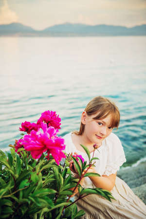 afterglow: Outdoor portrait of adorable little girl posing with bright pink peonies by lake Geneva, Switzerland