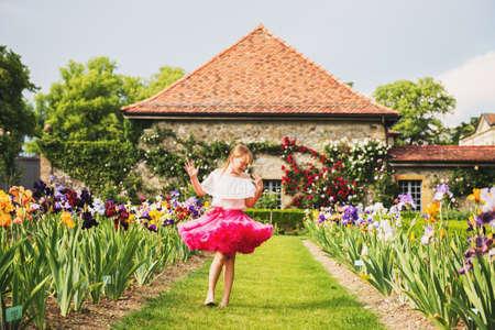 Sweet little kid girl dancing in a beautiful flower garden on a nice sunny summer day, wearing bright pink tutu skirt