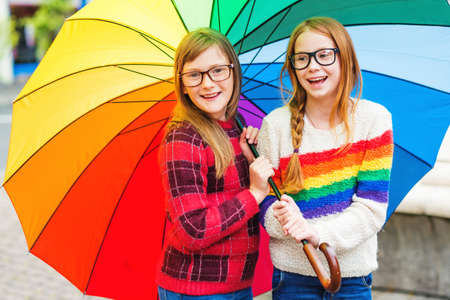 pullovers: Group of two cute little girls playing outside under big colorful umbrella, wearing glasses and warm pullovers Stock Photo