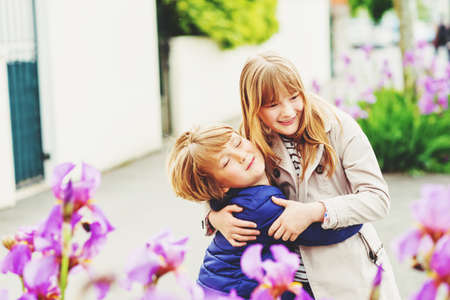 Two funny and happy kids playing together outdoors Stock Photo