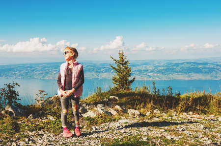 Cute little girl resting on the top of the mountain in french Alps with the view to Switzerland