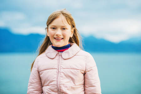Cute little 9-10 year old girl playing by the lake on a very windy day, wearing warm pink jacket Stock Photo