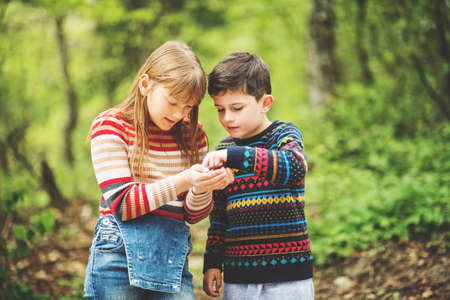 Cute kids playing together in a beautiful fresh spring forest Stock Photo