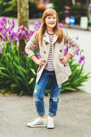 Outdoor fashion portrait of 9-10 year old hipster girl wearing stylish trench coat Stock Photo
