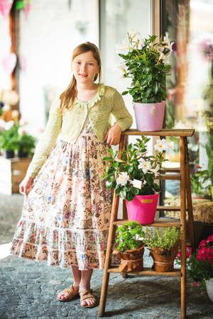 Openluchtportret van mooie 9-10 éénjarigenmeisje, die lange de zomerkleding draagt