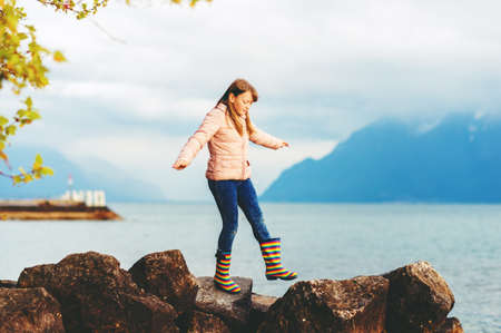 Adorable kid girl playing by the lake on a very cloudy day, wearing warm jacket and rain boots Stock Photo