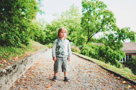 Handsome 3 year old boy playing in green park, wearing grey pullover and shorts Stock Photo