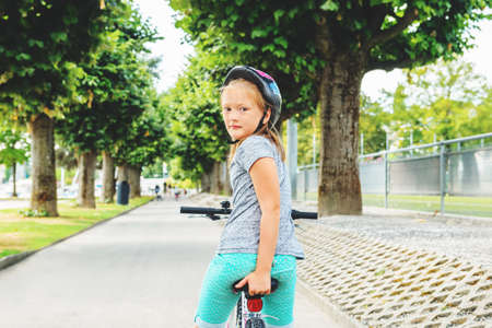 back alley: Kid girl sitting on the bicycle in the park, looking back over the shoulder Stock Photo