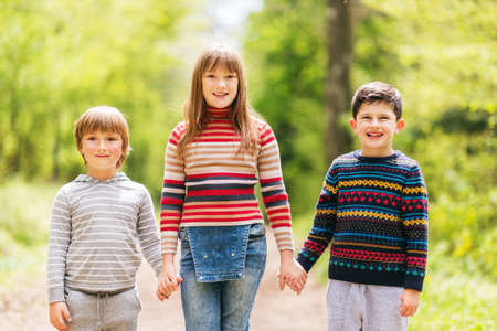 pullovers: Group of three happy kid hiking in spring forest, two boys and one girl playing together outside, wearing pullovers