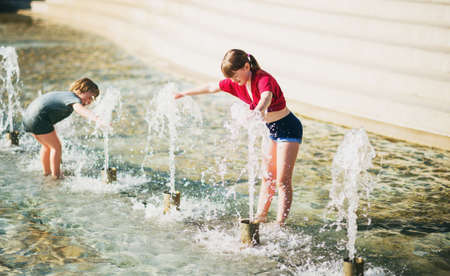 Two happy kids playing in public city fountain on a very hot day Stock Photo