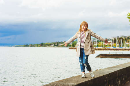Cute little girl playing outside on a cloudy day, wearing beige stylish trench coat. Image taken on Lake Geneva, Lausanne, Switzerland Stock Photo
