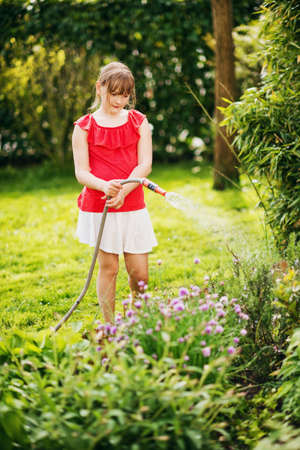 Kid girl watering plants in small garden Stock Photo
