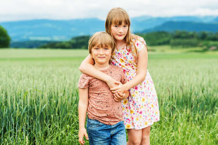 Two adorable kids playing together in summer wheat field