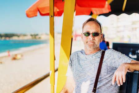 menton: Handsome man resting at seaside beach restaurant