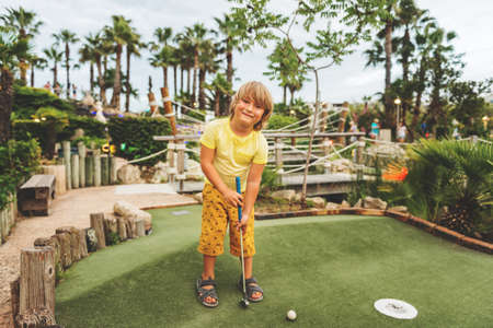 Funny kid boy playing mini golf, child enjoying summer vacation