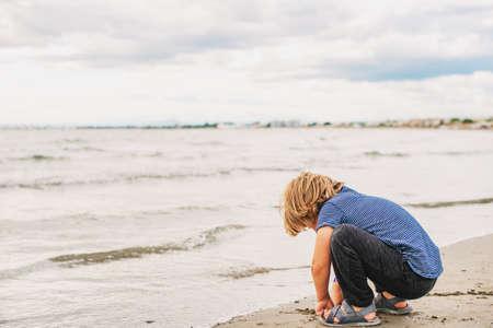 Schattige kleine jongen genieten van zomervakantie aan zee. Beeld dat in Le grau-du-Roi, het departement van Gard, Camargue in Languedoc-Roussillon, Frankrijk wordt genomen
