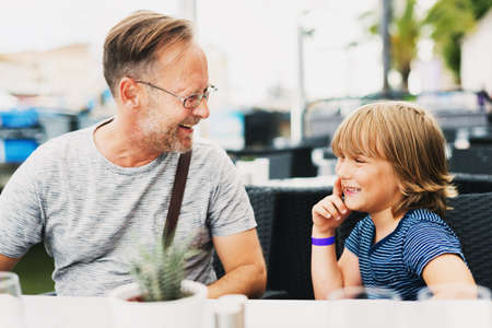 Happy father and son spending time together, resting in outdoor cafe