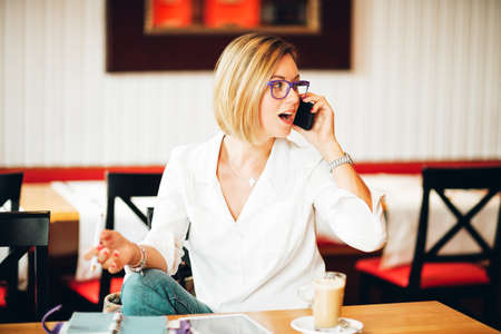 Candid portrait of a businesswoman working in a cafe, talking on the phone Banque d'images