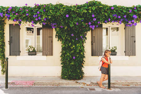 Funny little girl traveler walking on the streets of Provence, wearing backpack. Travel with kids, family vacation on south of France, image taken in Aigues-Mortes, Camargue Stock Photo