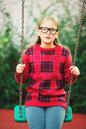 Outdoor portrait of a cute little 9 year old girl wearing eyeglasses  and red fashion pullover